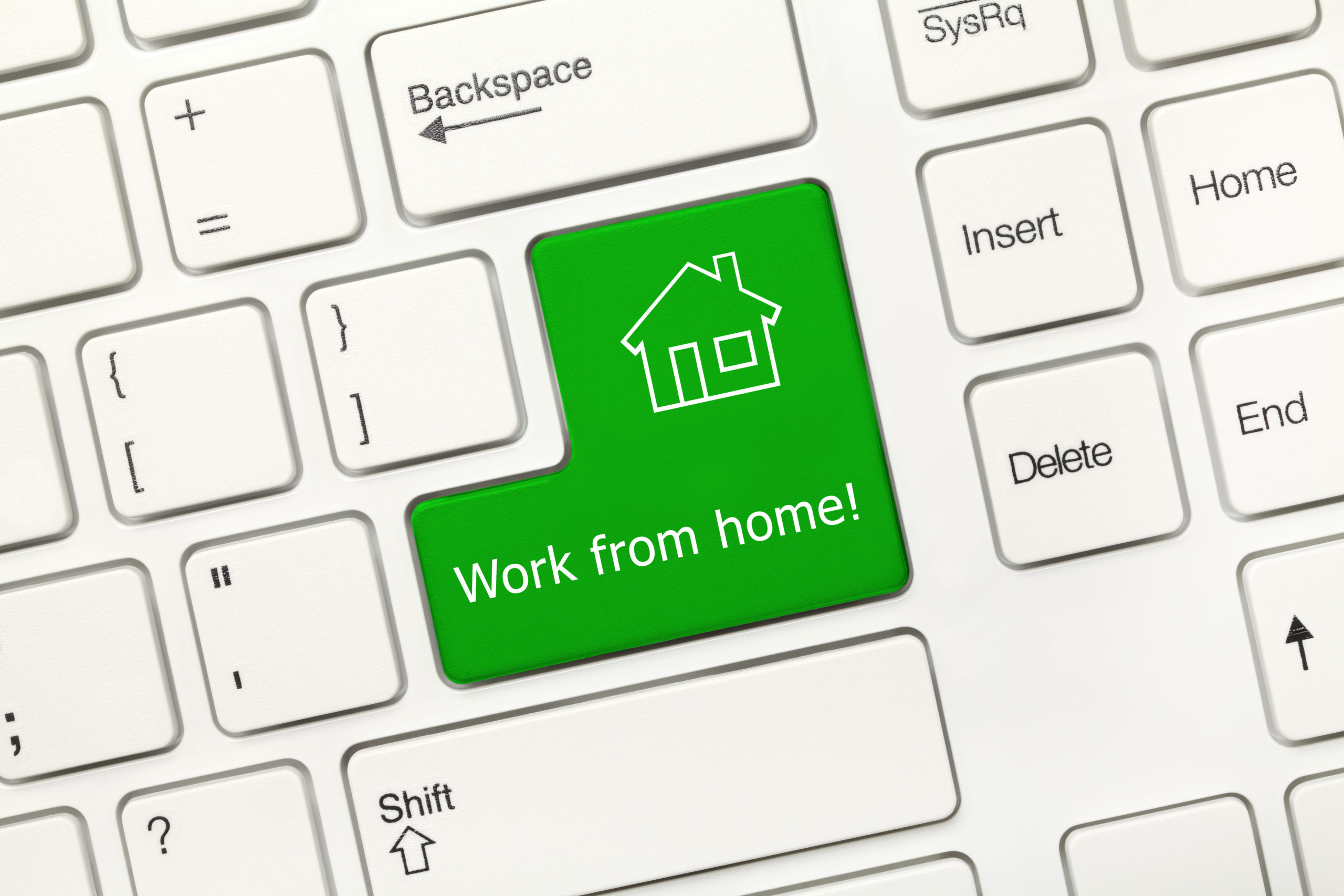 Close-up view on white conceptual keyboard - Work from home (green key)